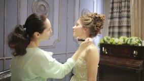 Se atusa a la novia antes de la boda chestFashion y maquillaje de los polvos metrajes