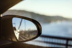 Se av det brovägen och havet reflekterade i backspegel, medan köra till och med bron fotografering för bildbyråer