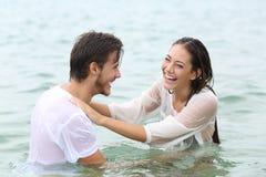 Se baigner de plaisanterie de couples drôles sur la plage images libres de droits