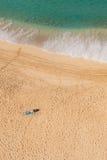 Se baigner de soleil d'homme en solo sur la plage reculée Images libres de droits