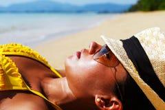 Se baigner de soleil de jeune femme sur une plage sablonneuse de la Thaïlande Image stock
