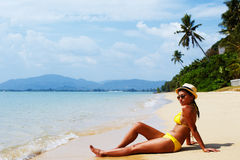 Se baigner de soleil de jeune femme sur une plage sablonneuse de la Thaïlande Photo libre de droits