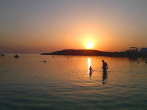 Se baigner en mer de soirée image stock