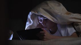 Se caçoa usando o PC da tabuleta sob a cobertura na noite O menino joga jogos de computador video estoque