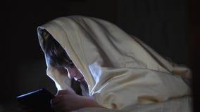 Se caçoa usando o PC da tabuleta sob a cobertura na noite O menino joga jogos de computador filme