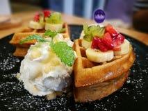 Se concentrer sélectif sur la gaufre avec l'écrimage glissé de fraise et de banane servi avec la crème à fouetter du plat noir images libres de droits