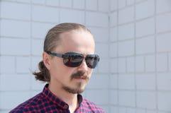 Se den bort manståenden Gladlynt skäggig hipsterman i svarta exponeringsglas Arkivfoto