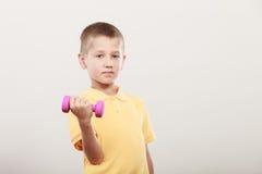 Se divierte al muchacho que hace ejercicio con pesa de gimnasia fotos de archivo