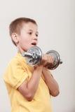 Se divierte al muchacho que hace ejercicio con pesa de gimnasia foto de archivo libre de regalías