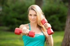 Se divierte ejercicio de la muchacha con pesas de gimnasia en el parque Foto de archivo libre de regalías