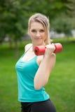 Se divierte ejercicio de la muchacha con pesas de gimnasia en el parque Imagen de archivo libre de regalías