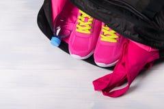 Se divierte el color rosado de las cosas para los deportes en un bolso en un fondo ligero Imagen de archivo libre de regalías