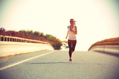 Se divierte el corredor de la mujer que corre en el camino de ciudad foto de archivo