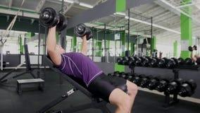 Se divierte entrenamiento duro de los músculos del entrenamiento del hombre joven del culturista en gimnasio Fotos de archivo libres de regalías