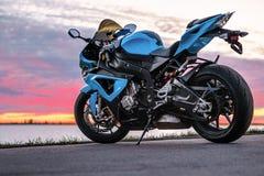 Se divierte la motocicleta en la orilla en la puesta del sol Foto de archivo libre de regalías