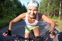 Se divierte a la muchacha con la bici Fotografía de archivo libre de regalías