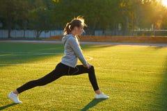 Se divierte a la muchacha que hace entrenamiento de la gimnasia de la mañana en hierba verde En el control de la luz del sol cali Fotos de archivo libres de regalías
