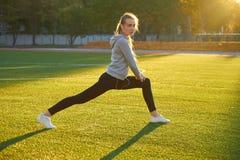Se divierte a la muchacha que hace entrenamiento de la gimnasia de la mañana en hierba verde En el control de la luz del sol cali Imagen de archivo libre de regalías