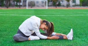Se divierte a la muchacha que hace entrenamiento de la gimnasia de la mañana en un campo de fútbol Aptitud, deporte, energía de l Imágenes de archivo libres de regalías