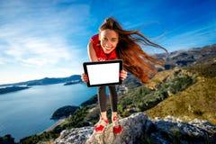 Se divierte a la mujer con la tableta digital en la montaña Fotografía de archivo libre de regalías