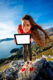 Se divierte a la mujer con la tableta digital en la montaña Fotos de archivo libres de regalías