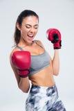 Se divierte a la mujer con los guantes de boxeo que celebra su victoria Imágenes de archivo libres de regalías