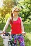 Se divierte a la mujer en la ropa de deportes con una bicicleta del deporte Fotografía de archivo