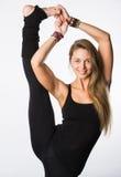 Se divierte a la mujer positiva en la ropa de deportes que coloca una pierna en el piso otra estirada hacia arriba, con emociones Imagen de archivo