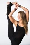 Se divierte a la mujer positiva en la ropa de deportes que coloca una pierna en el piso otra estirada hacia arriba, con emociones Fotos de archivo