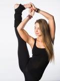 Se divierte a la mujer positiva en la ropa de deportes que coloca una pierna en el piso otra estirada hacia arriba, con emociones Fotografía de archivo