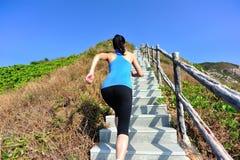 Se divierte a la mujer que corre en las escaleras de la montaña Foto de archivo libre de regalías