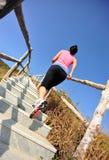 Se divierte a la mujer que corre en las escaleras de la montaña Imagenes de archivo