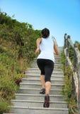 Se divierte a la mujer que corre en las escaleras de la montaña Fotos de archivo