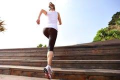 Se divierte a la mujer que corre para arriba en las escaleras de madera foto de archivo