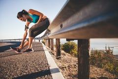 Se divierte a la mujer que estira después de correr al aire libre Fotos de archivo libres de regalías