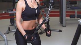 Se divierte a la mujer que hace ejercicio en la máquina de la cruce para el bíceps en gimnasio almacen de metraje de vídeo