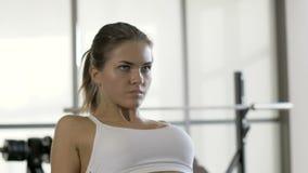 Se divierte a la mujer que tira del peso en el equipo de los fitnes en interior del club de deportes almacen de video