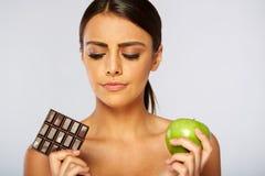 Se divierte a la mujer que toma la decisión entre la manzana sana Imágenes de archivo libres de regalías