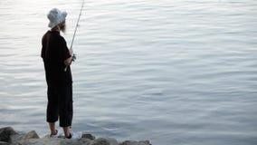 Se divierte la pesca del pescador en el río, usando señuelos de la pesca; almacen de metraje de vídeo