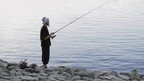 Se divierte la pesca del pescador en el río, usando señuelos de la pesca; metrajes