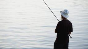 Se divierte la pesca del pescador en el río, usando señuelos de la pesca; almacen de video