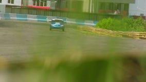 Se divierte las carreras de coches en pista, visión a través de la hierba verde almacen de metraje de vídeo