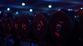 Se divierte pesas de gimnasia en club de deporte moderno sobre fondo del espejo almacen de metraje de vídeo