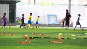 Se están entrenando vallas naranjas en un terreno artificial verde con entrenador borroso y fútbol infantil los futbolistas chico almacen de video