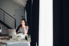 se för inspiration Ung härlig eftertänksam kvinna som gör några anmärkningar och ser bort, medan sitta i stol på henne Royaltyfri Fotografi
