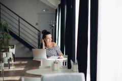 se för inspiration Ung härlig eftertänksam kvinna som gör några anmärkningar och ser till och med fönster, medan sitta in Royaltyfria Foton