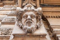 Se fasaden av den gamla byggnaden med skulpturen av ett manligt huvud Arkivbilder