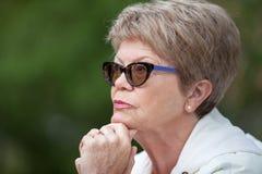 Se ferme vers le haut du portrait de vue de côté d'une femme agée en verres pensant avec la main sous la tête Photographie stock libre de droits
