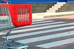 Se garer près du supermarché avec le chariot rouge à achats photographie stock libre de droits
