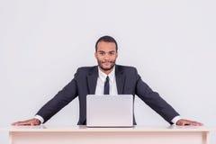 Se hace el trabajo Hombre de negocios africano sonriente que se sienta en la etiqueta Imágenes de archivo libres de regalías